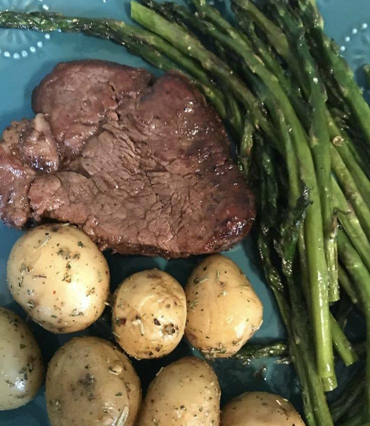 A steak, potatoes, and asparagus.